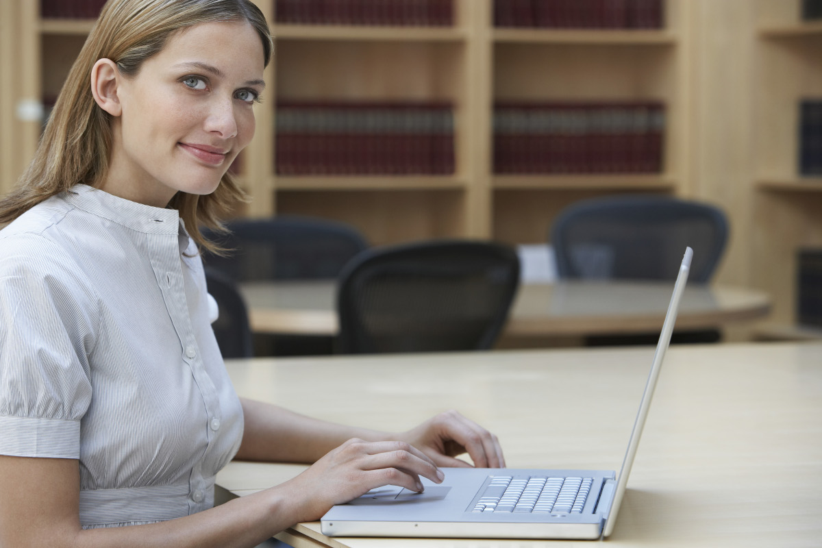 Office worker using laptop in legal office, portrait